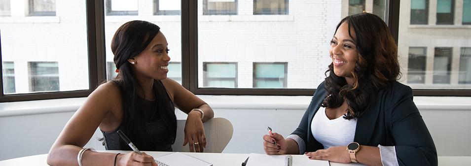 Two women talking in conference room
